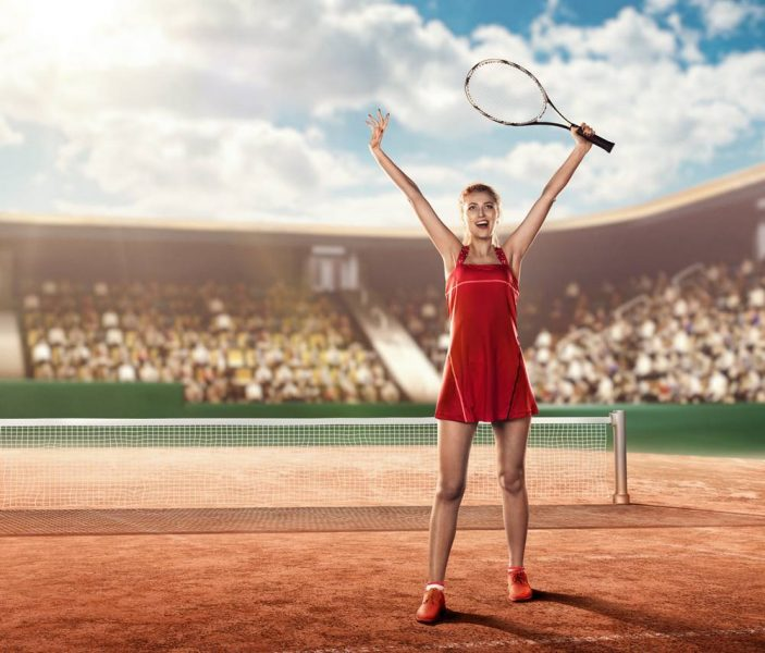 female tennis player on a tennis court holding a tennis racket above her head and celebrating a victory